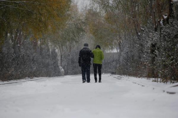 Đôi vợ chồng Fan Guohui và Zheng Quin đi về trên con đường tuyết phủ mù mịt sau khi viếng mộ con.