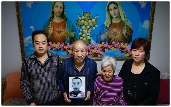 Vợ chồng cô Zhang đứng cùng cha mẹ già, họ cầm di ảnh đứa cháu nối dõi nhưng xấu số.