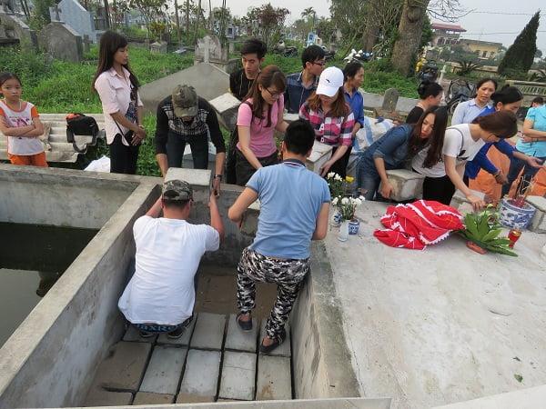 Các tình nguyện viên đặt quan tài xuống hố chôn tập thể cho các hài nhi. Ảnh: ML